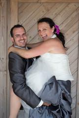 Wedding couple cuddling under wooden background