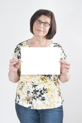 Attractive elderly woman holding a blank white sheet of paper fo