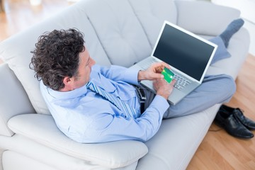 Businessman doing online shopping on couch