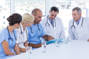 Doctor showing clipboard to his colleagues