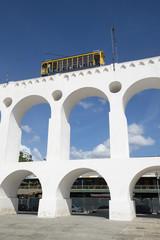 Bonde de Santa Teresa tram train drives along landmark white arches of Arcos da Lapa in Centro of Rio de Janeiro Brazil