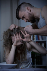 Man tearing wife's hair out