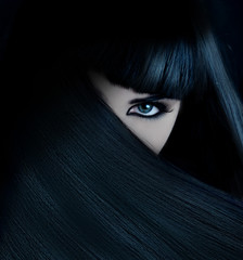 mysterious brunette wth hai covered face and aquamarine eyes