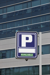 Parking signpost with available text and modern building backgro