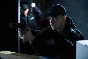 Policeman aiming gun during action