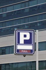 Parking signpost with full text and modern building background