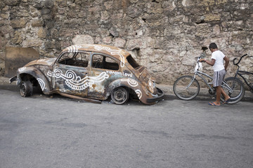 Scene at the entrance to the Vidigal favela in Rio de Janeiro features an old burned out ruined fusca car
