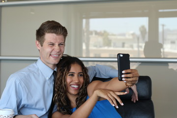 Pair of young executives looking at something fun on a cellphone