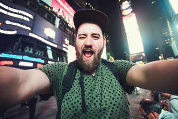 Funny bearded man posing, smiling and taking selfie photo on Times Square in New York while travel across USA