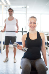 Woman Lifting Hand Weights in Brightly Lit Gym