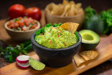 A delicious Bowl of Guacamole next to fresh ingredients on a table with tortilla chips and salsa Wall mural