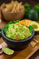 Guacamole and chips on a wood cutting board vertical shot restaurant style serving