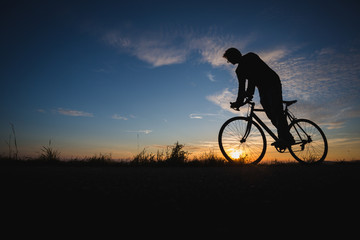 silhouetted cyclist in sunset