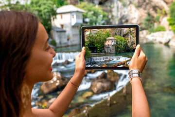 Woman photographing house on Buna spring in Blagaj village