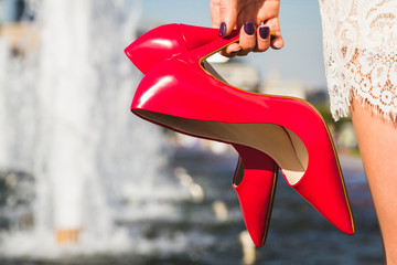 Female hand holding red shoes