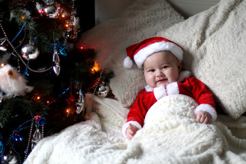 Baby at costume Santa at bed