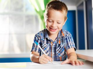happy little boy in his room doing home work