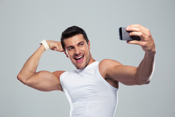 Cheerful sports man making selfie photo on smartphone