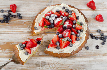 Fresh berry  cake on  a white   wooden background.