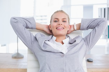 Smiling businesswoman relaxing on her office