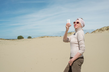 Extravagant woman doing selfie on vacation