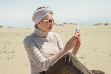 Woman in a turban sitting on sand and looking at the smartphone