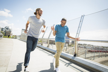 Two young men jogging along a bridge.