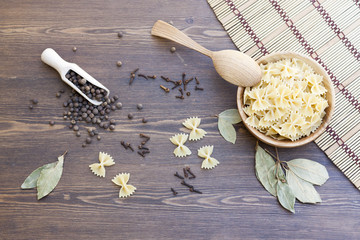 Pasta with herbs and spices on makisu and dark wooden table