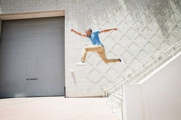 Young man jumping in the air down a stairway.