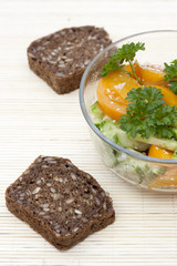 Salad with fresh vegetables and greens, whole wheat bread on a light makisu