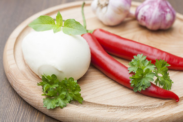 Mozzarella with herbs, noodles, fresh vegetables, chilli, garlic on a wooden round board, selective focus