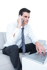 businessman talking on the phone on the sofa with his laptop