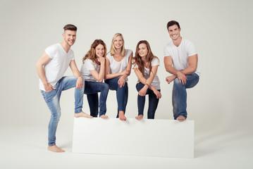 lachende gruppe steht mit den füßen auf einem weißen banner
