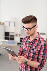 mann im büro schaut auf tablet-pc