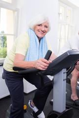 aktive seniorin im Fitnessstudio auf dem Fahrrad