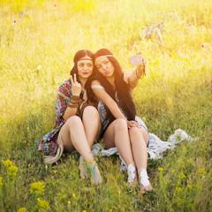 Two bohemian girls taking a selfie outdoors in summer