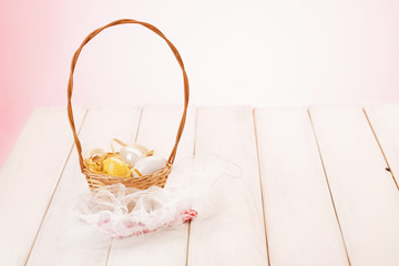 Easter eggs in basket/Basket with yellow and white eggs on picnic table