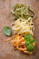 Close-up of italian tricolor pasta with basil, view from above