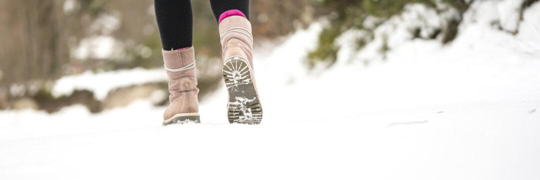 Winter adventures - closeup of warm female winter boots walking