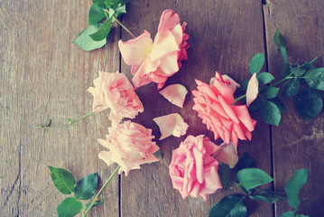 Vintage image of pink roses lying on the rustic wooden table. Photo filtered in faded, washed out, retro style. Romantic, nostalgic vintage concept.