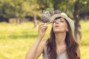 Young pretty caucasian woman having fun with blowing bubbles