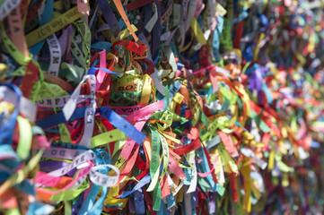 Colorful Brazilian wish ribbons tied to a fence at the Bonfim Church Salvador Bahia Brazil [translation: Memory of Bonfim Church]