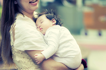 Asian mother hugging her baby outdoors