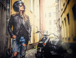 Female in blue jeans, leather jacket and motorcycle helmet