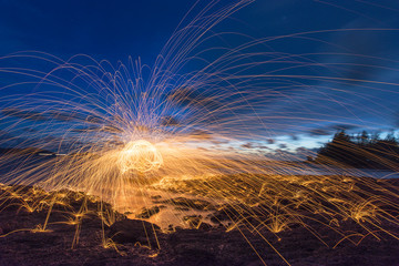 Amazing Fire dancing steel wool coast the sea in the twilight.