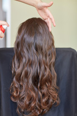 stylist with hair spray making hairdo at salon