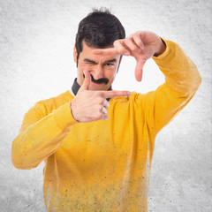 Man with moustache focusing with his fingers