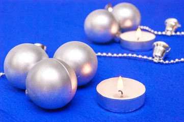 Silver Christmas balls and candles on a blue background