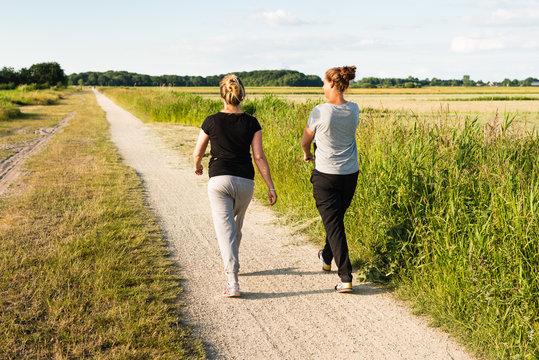 Two women walking on sandy path