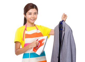 Housewife using the steam iron on suit jacket